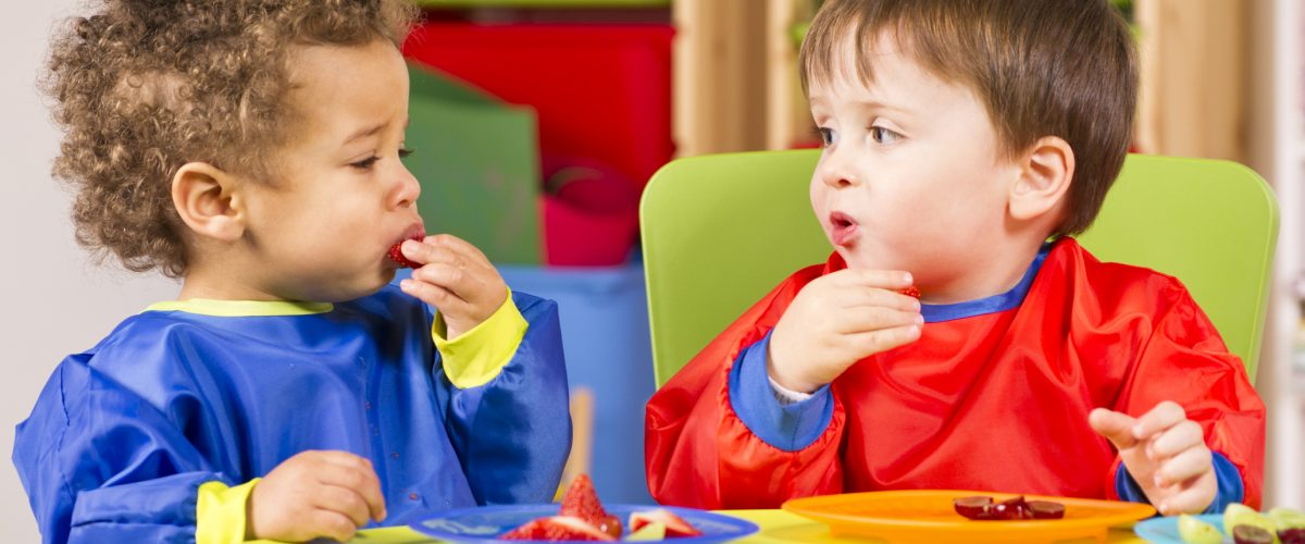 A stock photo of toddlers eating fruit and having a chat in the playroom.